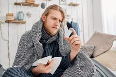 Kranker bärtiger blonder Mann im Sleepwear sitzt auf dem Bett, das durch Decke und Kissen, Stirnrunzeln beim Ablesen umgeben wird lizenzfreies stockbild