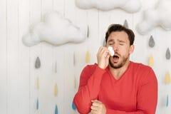 Kranker bärtiger Mann, der zu Hause niest Stockbild