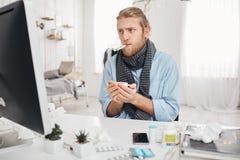 Kranker kranker bärtiger Mann sitzt vor Bildschirm mit Thermometer im Mund, Maßtemperatur, Griffe ein Schale von Stockfotos