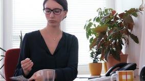 Kranker bei der Arbeit - ein junger Sekretär, der eine Pille für Kopfschmerzen einnimmt stock footage