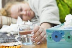 Kranker der jungen Frau im Bett, das ein Glas Wasser hält Stockfoto