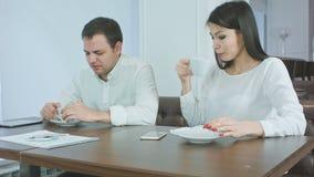 Kranker Geschäftsmann, der während besorgte Frau überprüft seinen Kopf auf Fieber und gibt ihm Serviette niest stock footage
