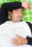 Kranker hispanischer Mann, der in Bett mit einem Thermometer legt Stockfotos