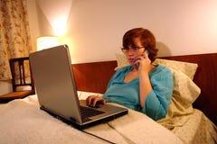 Kranker im Bett, das vom Haus arbeitet Stockfotografie
