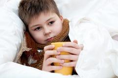 Kranker Junge, der im Bett liegt Lizenzfreie Stockfotografie