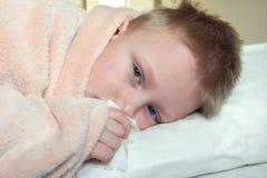 Kranker Junge, der im Bett liegt lizenzfreies stockfoto