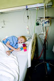 Kranker Junge im Krankenhausbett mit seinem Spielzeug Stockfoto