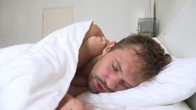 Kranker junger Mann mit dem Fieber schlafend im Bett, bedeckt durch eine Decke stockbilder