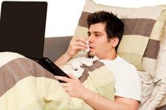 Kranker Kerl mit runny Wekzeugspritze unter Verwendung des Laptops auf der Couch Lizenzfreie Stockfotos