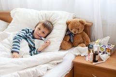 Kranker Kinderjunge, der im Bett mit einem Fieber, stehend liegt still stockbild