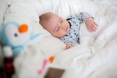 Kranker Kinderjunge, der im Bett mit einem Fieber, zu Hause stillstehend liegt stockfoto