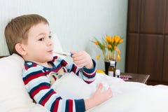 Kranker kleiner Junge, der im Bett mit Thermometer liegt Stockbild