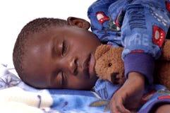 Kranker kleiner Junge, der mit seinem Teddybären schläft lizenzfreie stockfotos