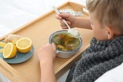 Kranker kleiner Junge, der Suppe isst, um Kälte im Bett zu kurieren stockfotografie