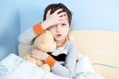 Kranker kleiner Junge umarmt seinen Teddybären im Bett Stockfoto