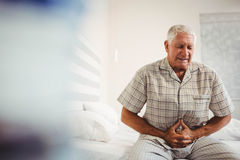 Kranker älterer Mann, der Magen hält Stockfoto