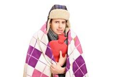 Kranker Mann abgedeckt mit der Decke, die eine Heißwasserflasche anhält Lizenzfreie Stockfotografie