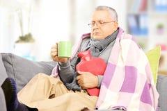 Kranker Mann auf einem Sofa bedeckt mit Decke heißen Tee zu Hause trinkend Lizenzfreie Stockfotos
