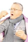 Kranker Mann bedeckt mit der Decke, die eine Pille einnimmt Lizenzfreies Stockbild