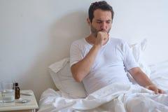 Kranker Mann, der auf Bett und dem Husten liegt Stockfotografie