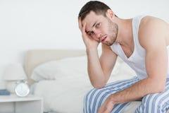 Kranker Mann, der auf seinem Bett sitzt Stockfotografie