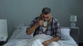 Kranker Mann, der im Bett, trinkender fiebervermindernder Tee hustet, um Fieber, Grippeepidemie zu behandeln stock footage