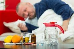 Kranker Mann im Bett mit Drogen und Frucht auf Tabelle Lizenzfreies Stockfoto