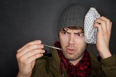 Kranker Mann mit Eissatz und -thermometer lizenzfreie stockbilder