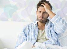 Kranker Mann mit Thermometer im Mund, der zu Hause auf Bett sitzt Lizenzfreies Stockfoto
