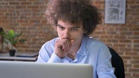 Kranker nerdy Büroangestellter, der an dem Laptop, sitzend im modernen Büro mit Backsteinmauerhintergrund hustet und arbeitet stock footage