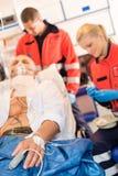 Kranker Patient mit Sanitäter in der Krankenwagenbehandlung Lizenzfreies Stockbild