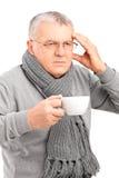 Kranker reifer Mann, der eine Tasse Tee anhält und Kopfschmerzen gestikuliert Lizenzfreies Stockbild