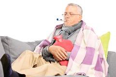 Kranker Senior, der seine Körpertemperatur misst stockfotografie