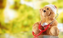 Kranker Teddy Bear mit Stethoskop auf Glastisch stockbilder