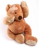 Kranker Teddybär mit Pflaster auf seinem Kopf. Stockfotos