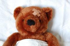 Kranker Teddybär mit Verletzung im Bett Lizenzfreie Stockfotos