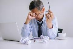 Kranker und müder, älterer Geschäftsmann deprimiert und, Geschäftsmann an seinem Schreibtisch erschöpft frustriert mit Problemen  lizenzfreie stockbilder