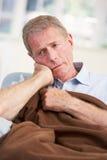 Kranker, unglücklicher älterer Mann zu Hause Stockbilder