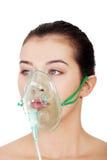 Kranker weiblicher Patient, der eine Sauerstoffmaske trägt Lizenzfreie Stockbilder