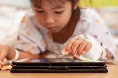 Krankes asiatisches kleines Kindermädchen, das die Lösung IV haben, die digitale Tablette spielend, um sich zu entspannen verbund stockfotografie
