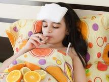 Krankes junges Mädchen im Bett mit Thermometer Lizenzfreies Stockfoto