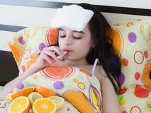 Krankes junges Mädchen im Bett mit Thermometer Stockfotografie