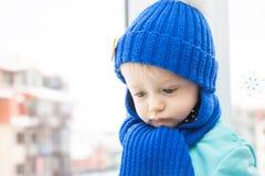 Krankes Kind in der warmen Kleidung mit traurigem Blick während der Winterurlaube im Haus gegenüber von dem Fenster, möchten zu g stockfoto