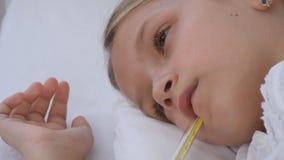 Krankes Kind im Bett, krankes Kind mit Thermometer, Mädchen im Krankenhaus, Pillen-Medizin stockfoto