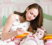 Krankes Kind mit dem hohen Fieber, das in das Bett und in Mutter nehmen Tempera legt Stockbild