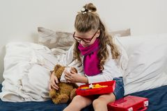 Krankes Kindermädchen in den Gläsern, heilt seinen kranken Teddybären Stockfotos