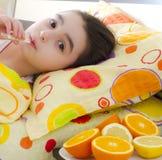 Krankes kleines Mädchen mit einem Thermometer im Bett Stockbilder