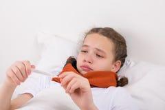 Krankes Mädchen, Blicke bei der Temperatur auf einem Thermometer, liegend im Bett lizenzfreie stockfotos
