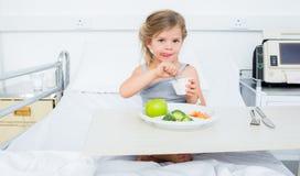 Krankes Mädchen, das gesundes Lebensmittel im Krankenhaus isst Lizenzfreie Stockfotos