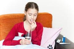 Krankes Mädchen, das im Bett einnimmt Medizinpillen mit Wasserglas liegt Lizenzfreie Stockfotos